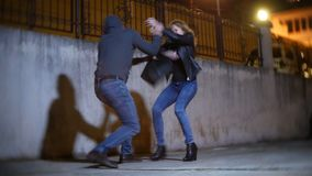 A male robber, threatens a woman and takes her purse, in a dark alley. at night. A male robber, threatens a women and takes her purse, in a dark alley. at night stock images