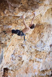 Male rock climber on challenging route on cliff Stock Photos