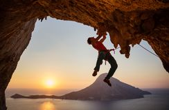Male rock climber on challenging route on cliff at sunset. Male rock climber on challenging route on cliff in cave at sunset royalty free stock image