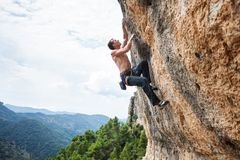 Male rock climber on challenging route on cliff Stock Image