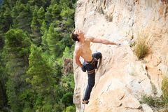 Male rock climber on challenging route on cliff Royalty Free Stock Photo