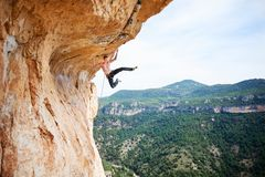 Male rock climber on challenging route on cliff Stock Photo