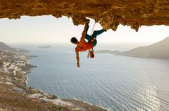 Male rock climber on challenging route going along ceiling in cave. Kalymnos, Greece royalty free stock photography