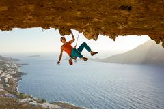 Male rock climber on challenging route going along ceiling in cave. View of coast below stock photo