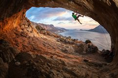 Male rock climber climbing along a roof in a cave Stock Photo