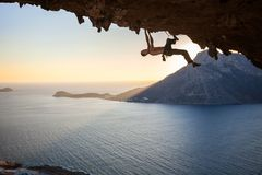 Male rock climber climbing along a roof in a cave. At sunset Royalty Free Stock Photos