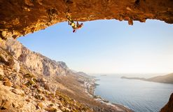 Male rock climber climbing along a roof in a cave Stock Images