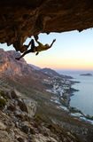 Male rock climber climbing along a roof in a cave Royalty Free Stock Photography