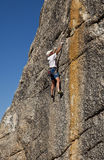 Male rock climber clings to a cliff. Stock Photo