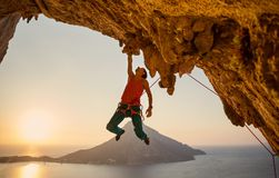 Male rock climber hanging with one hand on challenging route on cliff. At sunset stock images