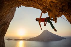 Male rock climber hanging with one hand on challenging route on cliff. At sunset royalty free stock image