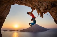 Male rock climber hanging with one hand on challenging route on cliff. At sunset stock photo