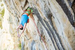 Young man resting while climbing challenging route on overhanging cliff. Male rock climber hanging upside down on challenging route, resting before keeping on royalty free stock photo