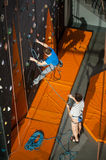 Male rock-climber practicing climbing on rock wall indoors Royalty Free Stock Image