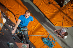 Male rock-climber practicing climbing on rock wall indoors Stock Images