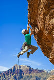 Male rock climber reaching for the summit. Stock Images