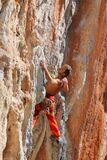 Rock climber leaging climbing route on natural rock