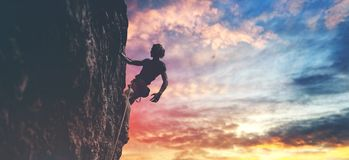 Male rock climber resting while climbing the challenging route on the rocky wall. Man rock climber with long hair. side view of young man rock climber in bright stock image