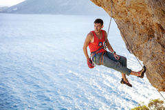 Male rock climber resting while hanging on rope Stock Photo