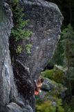 Male rock climber struggles to climb a challenging overhanging. Extreme sport climbing. Stock Image