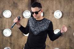 Male rock singer performs on scene in projectors lights. Male singer of rock or pop music dressed in black and sunglasses with microphone performs on scene with Royalty Free Stock Photography