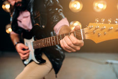 Male rock star with electro guitar on the stage Royalty Free Stock Image