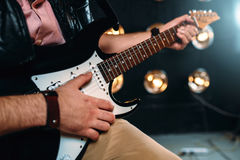 Male rock star with electro guitar on the stage Stock Photo