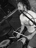 Male rock vocalist drummer singing close to a microphone stand playing the drums in black and white stock images