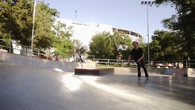 Male roller skater practices tricks and moves in the modern skate outdoors park. Young man engaged in extreme sport. Exercising with inline roller skates stock video