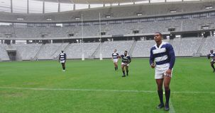 Male rugby player kicking rugby ball in ground at stadium 4k. Front view of African American male rugby player kicking rugby ball in ground at stadium. They are stock footage