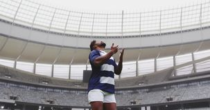Male rugby player playing rugby match in stadium 4k. Low angle view of male rugby player playing rugby match in stadium. He is catching rugby ball 4k stock video