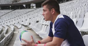 Male rugby player sitting with rugby ball in stadium 4k. Side view of Caucasian male rugby player sitting with rugby ball in stadium. He is upset and looking stock video