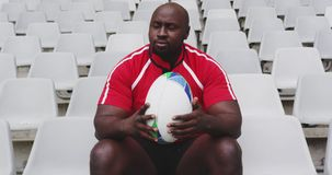 Male rugby player sitting with rugby ball in stadium 4k. Front view of African American male rugby player sitting with rugby ball in stadium. He is looking away stock footage