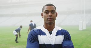 Male rugby player standing with arms crossed in stadium 4k. Front view of African american male rugby player standing with arms crossed in stadium. He is looking stock video
