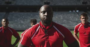 Male rugby player standing with hands on hip in stadium 4k. Close-up of African American male rugby player standing with hands on hip in stadium. He is tired and stock video footage