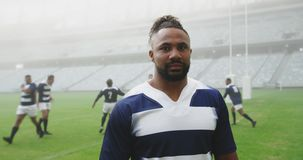 Male rugby player standing in stadium 4k. Front view of African american male rugby player standing in stadium. He is looking at camera 4k stock footage