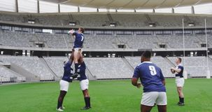 Male rugby players playing rugby match in stadium 4k. Side view of diverse male rugby players playing rugby match in stadium. They are passing rugby ball 4k stock video footage