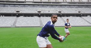 Male rugby players playing rugby match in stadium 4k. Side view of male rugby players playing rugby match in stadium. They are passing ball to each other 4k stock footage