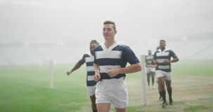 Male rugby players running in the stadium 4k. Front view of diverse male rugby players running in the stadium. They are warming-up 4k stock video footage