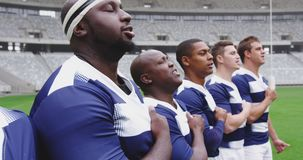 Male rugby players taking pledge together in stadium 4k. Close-up of diverse male rugby players taking pledge together in stadium. They are looking away 4k stock video footage