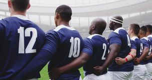 Male rugby players taking pledge together in stadium 4k. Rear view of diverse male rugby players taking pledge together in stadium. They are arm around 4k stock footage