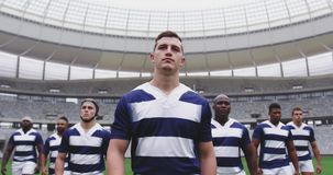 Male rugby players walking together in the stadium 4k. Low angle view of diverse male rugby players walking together in the stadium. They are looking away 4k stock video