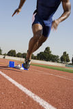 Male Runner Beginning Race From Starting Blocks. Low section of African American male runner beginning race from starting blocks Royalty Free Stock Images