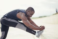 Male runner in black sportswear stretching legs before doing morning workout. Royalty Free Stock Image