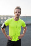 Male runner in bright sportswear posing at the stadium while listening to music in headphones on his smart phone Royalty Free Stock Image