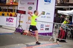 Male runner celebrates finish of marathon. KYIV, UKRAINE - APRIL 28: Male runner celebrates finishing during 5-th Wizz Air Kyiv City Marathon, a competition run Royalty Free Stock Photography