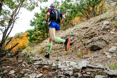 Male runner in compression socks. Running on a mountain trail. backpack for running behind his back Royalty Free Stock Photo
