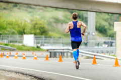 Male runner in compression socks running in road with traffic cones safety. Rosa Khutor, Russia - May 7, 2017: male runner in compression socks running in road Stock Photo