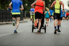 Male runner dad running with baby carriage. Male runner dad running with  baby carriage on street city marathon Stock Photography