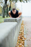 Male runner doing exercise, workout in the fall park. Push ups with bench. Male runner doing exercise, preparing for morning workout in the fall park. Push ups Stock Photo